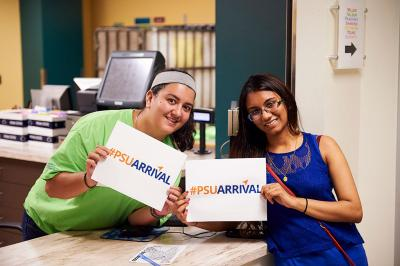 Two female students promoting #PSU-Arrival with signs at a workstation.