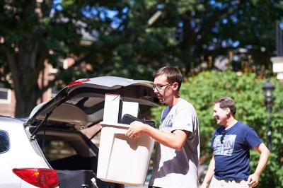 Male student unpacking car and carrying a container