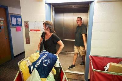 Woman exiting elevator with a load of moving items at dorm.