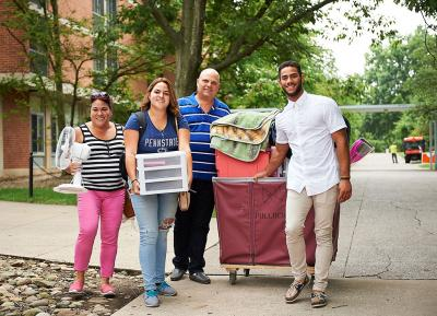 People posing for picture outside dorm holding moving items.