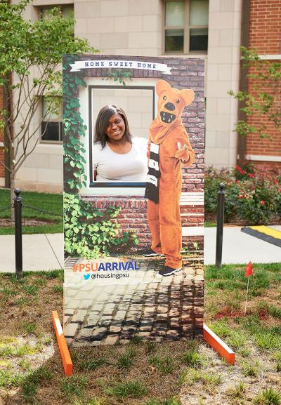 Female Student taking picture with Nittany Lion Cutout