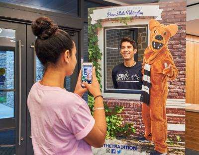 Woman taking picture of man posing with Nittany Lion cutout.