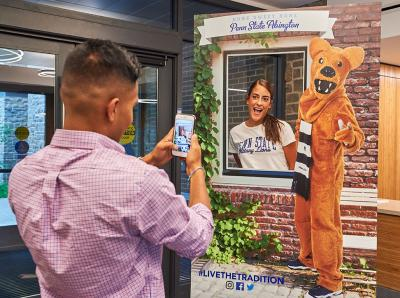 Man taking picture of woman posing with Nittany Lion cutout.