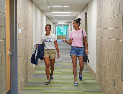 Two women walking toward camera in a dorm hallway.