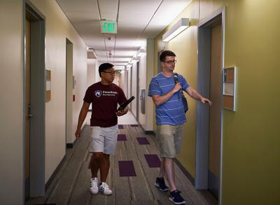 Two men walking toward camera in a dorm hallway.