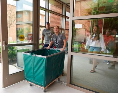 Woman exiting a dorm with an empty cart walking toward camera.