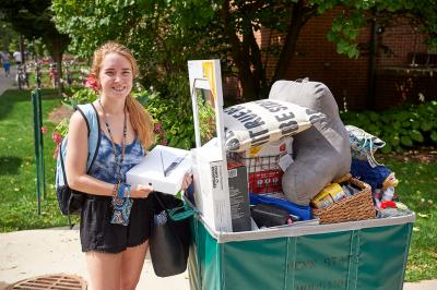 Woman standing next to a cart loaded with her belongings outside on a sidewalk.