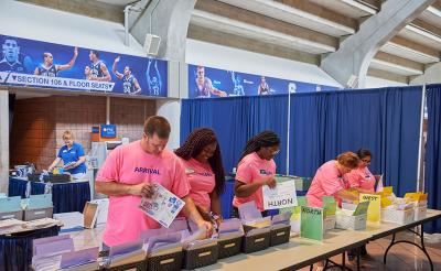 People with Arrival Teeshirts organizing files at a check-in station.