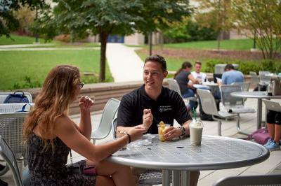 Male and Female student sitting at table eating and smiling.